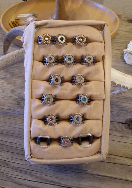 Assorted rings made by Anna Steinhoff, Many feature the primer cut from the end of a used bullet shell